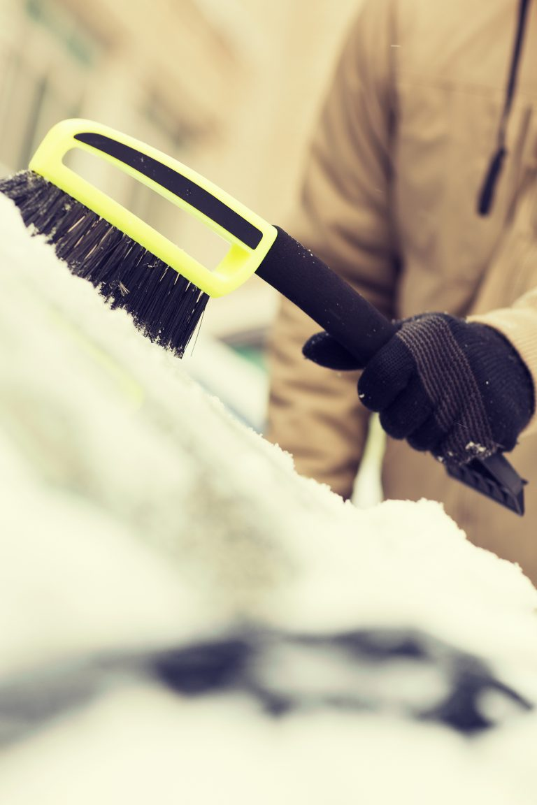transportation, winter and vehicle concept - closeup of man cleaning snow from car windshield with brush